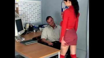 شابة طويلة ، ترتدي ملابس فاتحة للشهية وتتسلق على مكتب وتسمح لنفسها بالاختراق