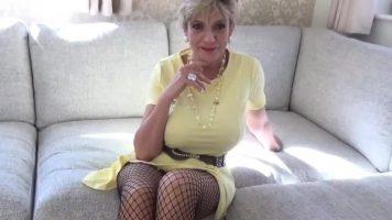 امرأة شقراء مع كبير الثدي ترتدي تنورة قصيرة وتبحث عن الديك